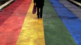 pedestrian walks across rainbow crossing in Sydney