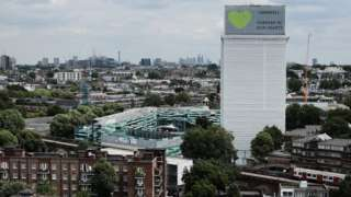 """A sign with """"Grenfell Forever In Our Hearts"""" is displayed on the top of Grenfell Tower"""