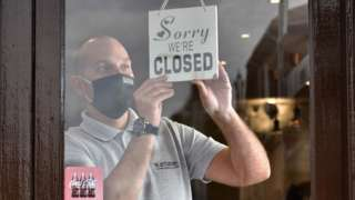 """A man puts a """"closed"""" sign in the window of his cafe"""