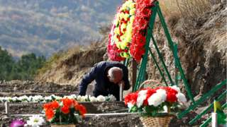 A man mourns at the grave of a fallen soldier, who was killed during the military conflict over the breakaway region of Nagorno-Karabakh, in Stepanakert 14 October, 2020.