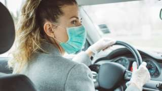 Woman wearing a face mask, driving a car