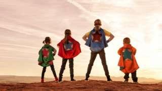 Siblings dressed as superheroes