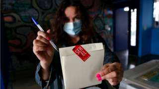 A Chilean woman shows her votes during the Constitutional Convention Election