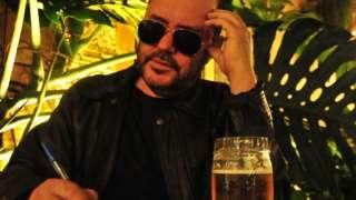 Toninho Geraes sentado diante de mesa, escrevendo e de óculos escuro