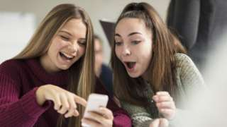 Two teenage girls point and laugh at a smartphone screen in this stock photo