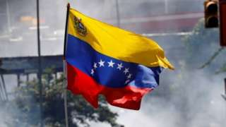 """A demonstrator waves a Venezuelan flag during riots at a march to state Ombudsman""""s office in Caracas, Venezuela May 29, 2017."""