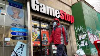 A man in a mask walks past a GameStop store in NY