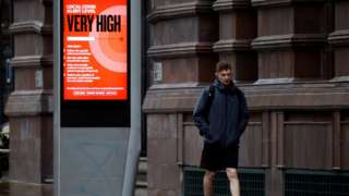 A man walks past a sign about COVID-19 measures, amid the outbreak of the coronavirus disease (COVID-19), in Manchester