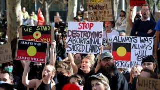 Protesters are seen during a rally outside the Rio Tinto office in Perth