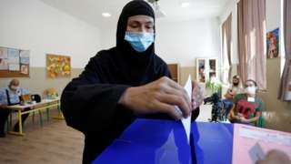 A woman wearing a face mask casts her vote in Montenegro