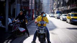 A Meituan delivery worker wearing a face mask is seen on a street following an outbreak of the coronavirus disease (COVID-19) in Shanghai, China January 13, 2021.