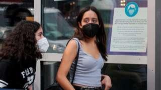 纽约市街头两位少女戴着口罩走过一家商店(27/7/2021)