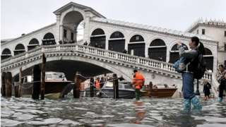 A tourist takes a photo from the flooded embankment by the Rialto bridge in Venice, 13 November 2019