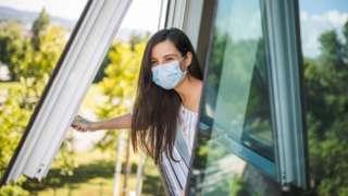 Mujer con una mascarilla abriendo una ventana