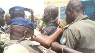 Baye Modou Fall being taken to the police station
