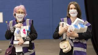 Two women in face masks carry hand sanitiser and other Covid cleaning products