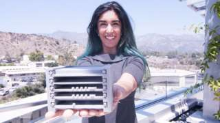 A woman with long, dark brown and green hair stands in front of a mountainous background holding out a grey, 3D printed model