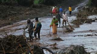 People attempt to cross the waters of a flash flood at Solai after the banks of a dam burst its banks