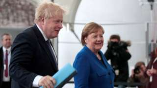 Boris Johnson is greeted by Angela Merkel as he arrives in Berlin for a summit about Libya, in January 2020