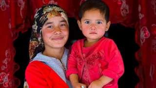 Một phụ nữ Duy Ngô Nhĩ với đứa con của mình ở chợ Serik Buya, Yarkand, Khu tự trị Duy Ngô Nhĩ Tân Cương, Trung Quốc vào ngày 20 tháng 9 năm 2012 tại Yarkand, Trung Quốc.