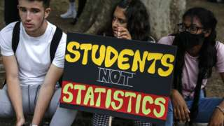 """Three students sit on a street kerb with a protest placard reading: """"students not statistics"""""""