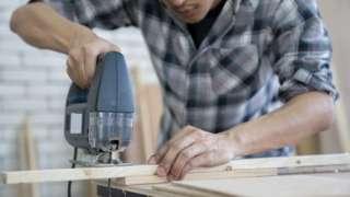 A man sawing timber