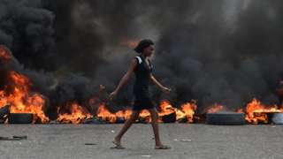 A woman walks past tire barricades set ablaze by demonstrators on the fourth day of protests in Port-au-Prince