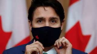 Canadian Prime Minister Justin Trudeau puts on a mask at a news conference held to discuss the country's coronavirus disease