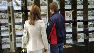 Couple look in estate agent's window