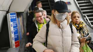 Woman wearing mask on the Tube