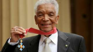 Earl Cameron outside Buckingham Palace with his CBE
