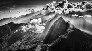 Black and white photograph of a cloud above mountains