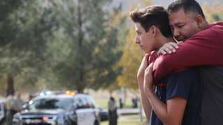 A father hugs his son after reuniting at a park near Saugus High School