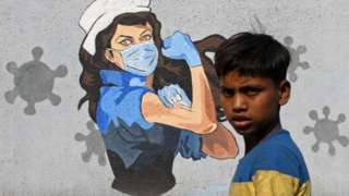 A boy walks past a graffiti painted to create awareness about the coronavirus disease.