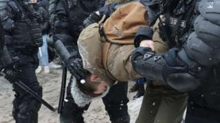 Protester held by police officers