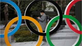 A man looks at his mobile phone next to The Olympic rings in front of the Japan Olympics Museum in Tokyo, Japan, March 4, 2020.