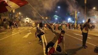 Foto noturna mostra manifestante com bandeira do Peru caindo no asfalto