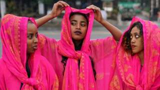 Three women dressed in traditional dresses of the Harari culture of eastern Ethiopia