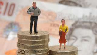 Man and woman stand on piles of coins