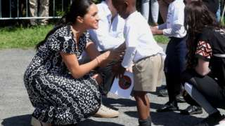 Meghan speaks to a young boy on a visit to Cape Town's Nyanga township