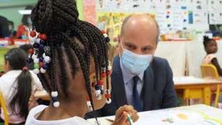 O ministro de educação da França, Jean-Michel Blanquer, de máscara, conversa com uma menina de tranças no cabelo, sentada em sua carteira, na escola