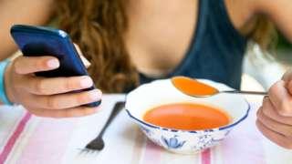 Jovem sentada diante de mesa, uma mão segurando collher de sopa, outra um celular