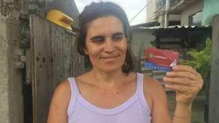 Kátia sorri e segura sorrindo o cartão mumbuca, em frente a portão de casa