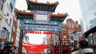 A person takes a picture of decorations set up for Chinese Lunar New Year in China Town, London, Britain February 11, 2021.