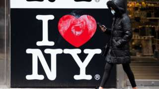 A woman walking past an 'I love New York' sign