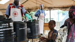 A young girl washes her hands in an Ebola prevention checkpoint supported by UK aid at a Ugandan border crossing point with the DRC, August 2019