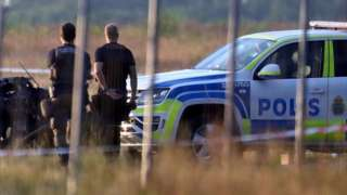 Police officers observe a small aircraft that crashed at Orebro Airport, Sweden