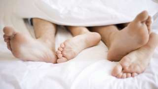 Unidentified young couple in bed, sleeping, sleep, embrace beneath a duvet, bare feet sticking out