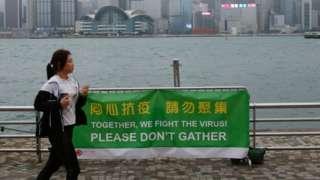 """香港九龙尖沙咀一位正在跑步女士经过一面""""同心抗疫请勿聚集""""横幅(2/4/2020)"""