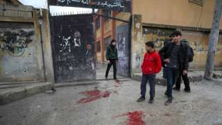 People stand next to patches of blood outside a school in the opposition-held town of Sarmin, Syria, that was reportedly hit by cluster munitions fired by government forces (1 January 2020)
